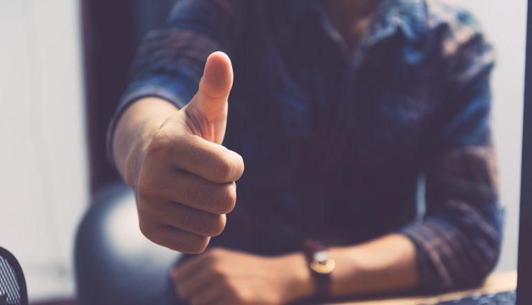Man holding thumb up to show positivity