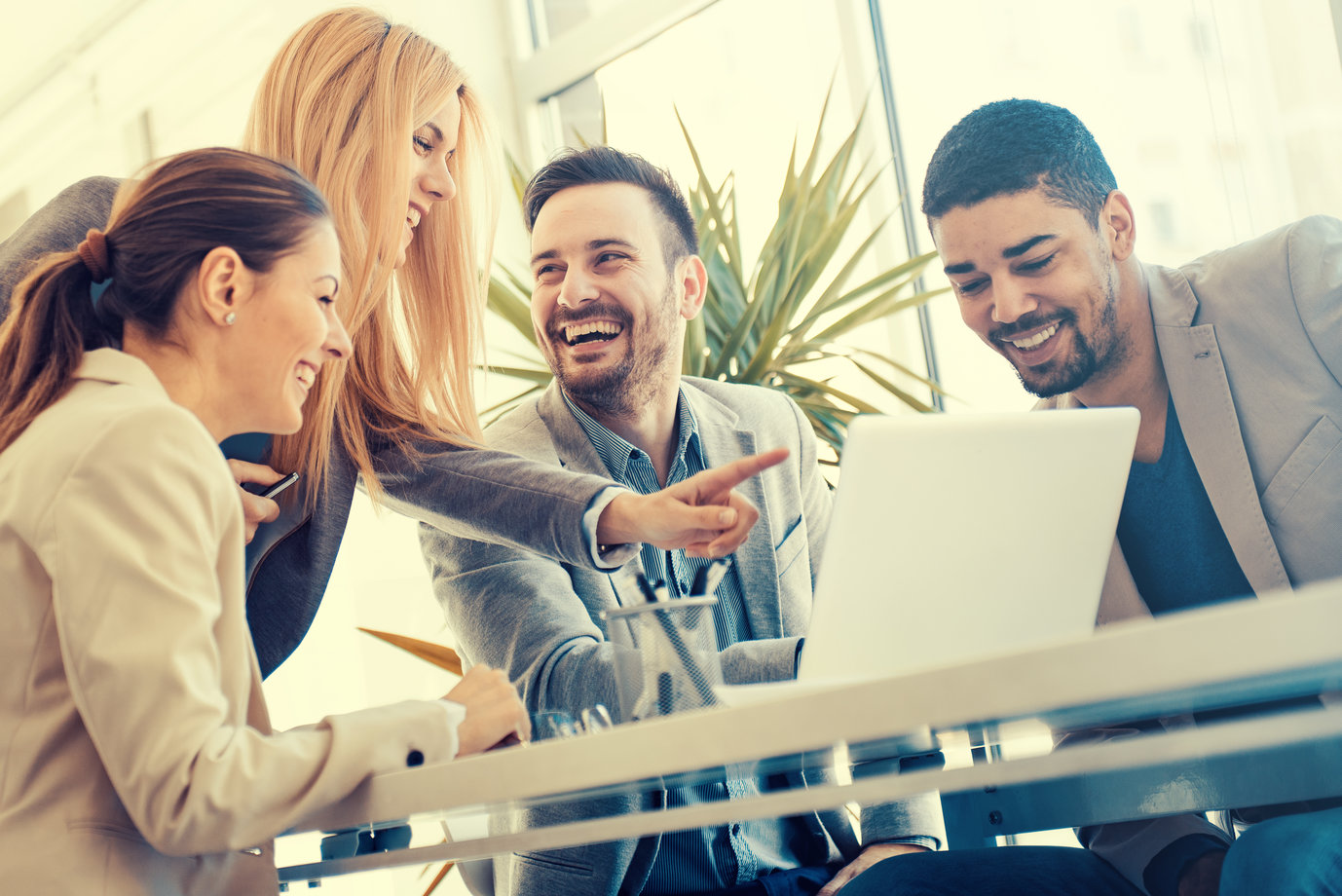 Work colleagues laughing and looking at laptop