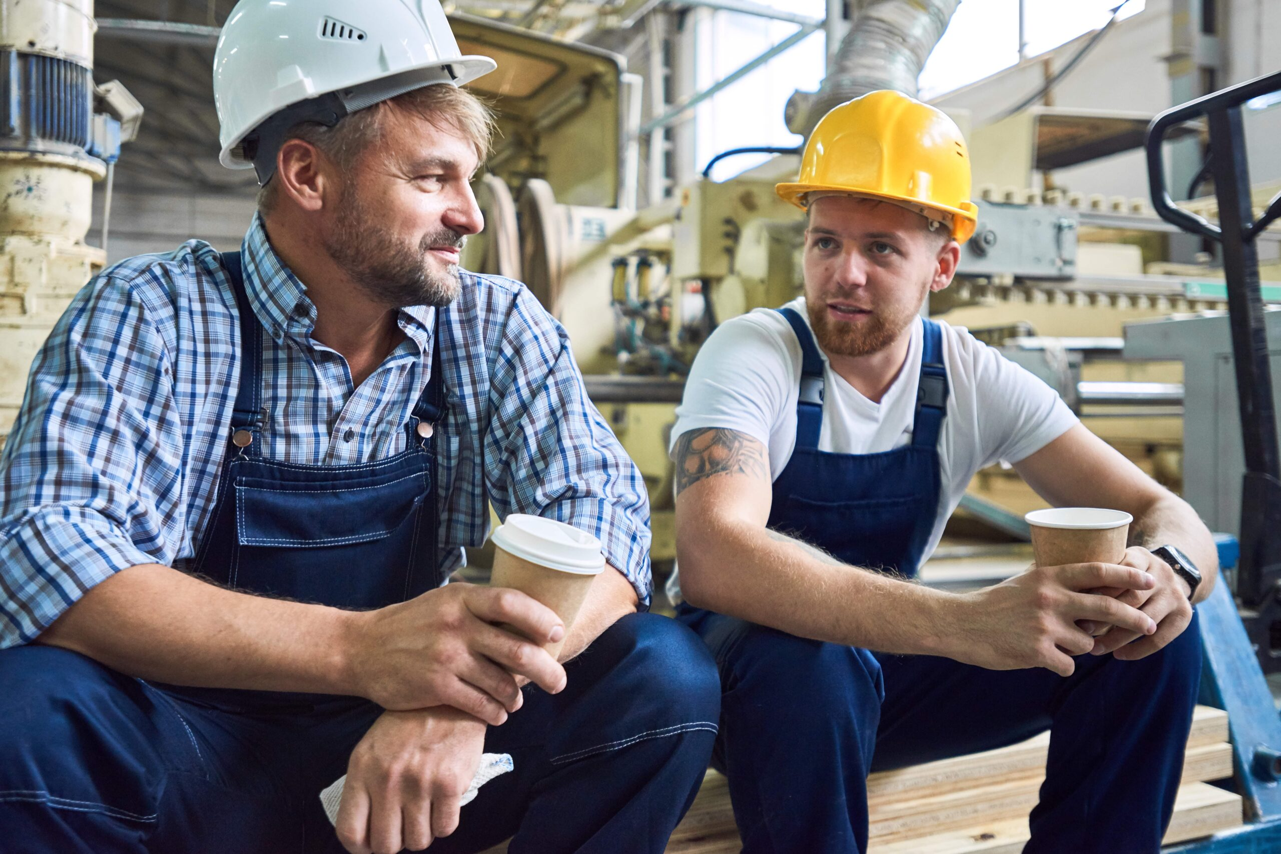 Two builders talking over coffee